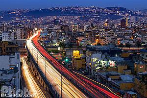 Photo : Circulation automobile la nuit sur une autoroute urbaine (Rue de l'Indépendance) et Bourj Hammoud la nuit vue depuis Beyrouth, Liban