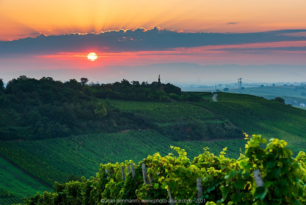 Sunrise above the statue of the Sacred Heart in Wolxheim